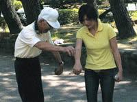 ペタンク初挑戦の和田由樹健康リポーター。 まずは、プールと呼ばれる金属の球の握り方から教えてもらう