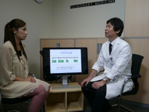 COPDの原因は長年の喫煙と話す、井上博雅教授(右)と藏薗千尋リポーター